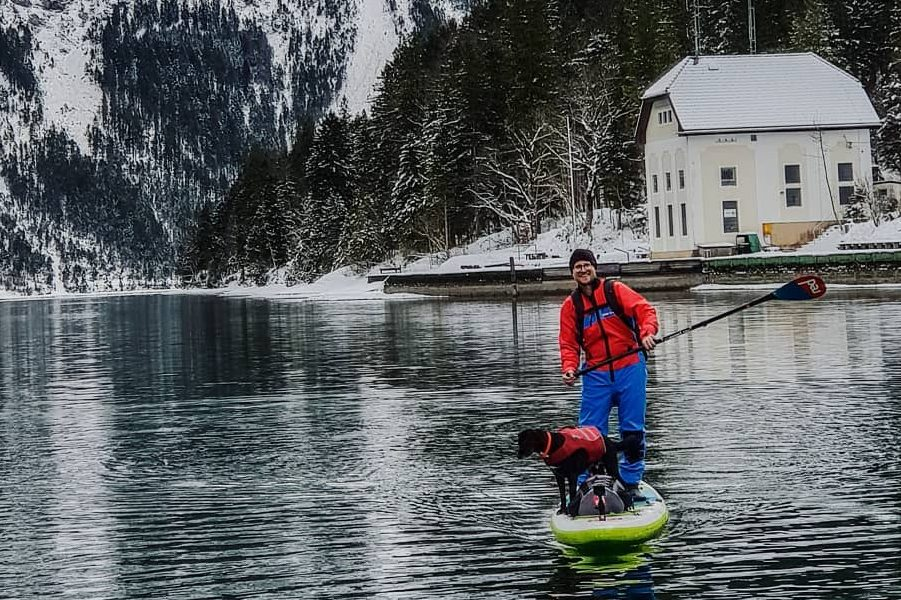 man and dog paddle boarding at Eibsee, Germany surrounded by snow capped mountains