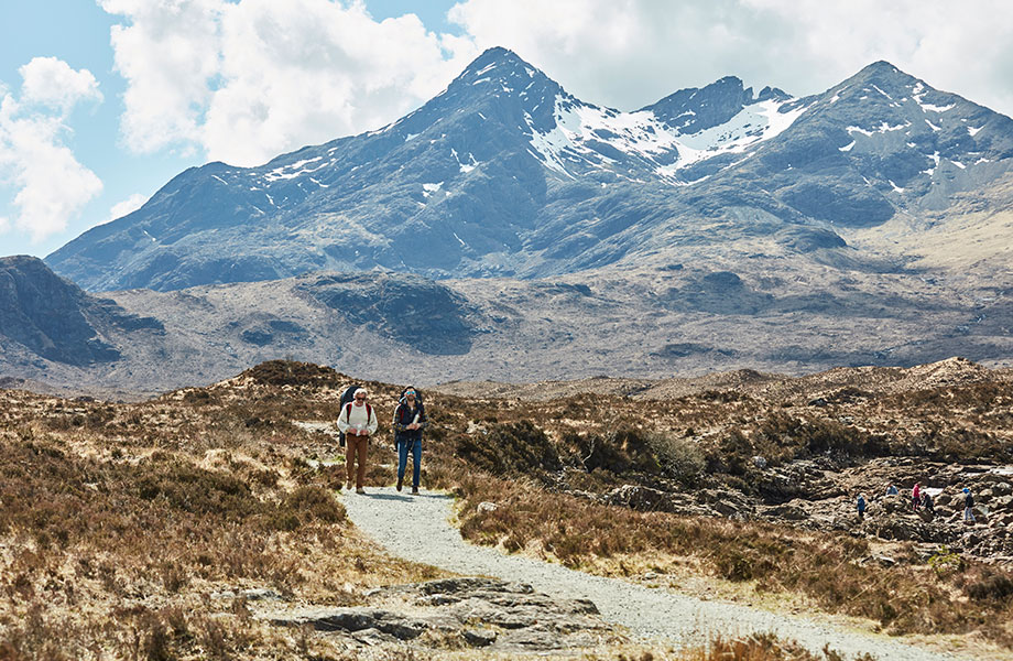 two men hike along path with their backpacks with giant snowcapped mountains in background
