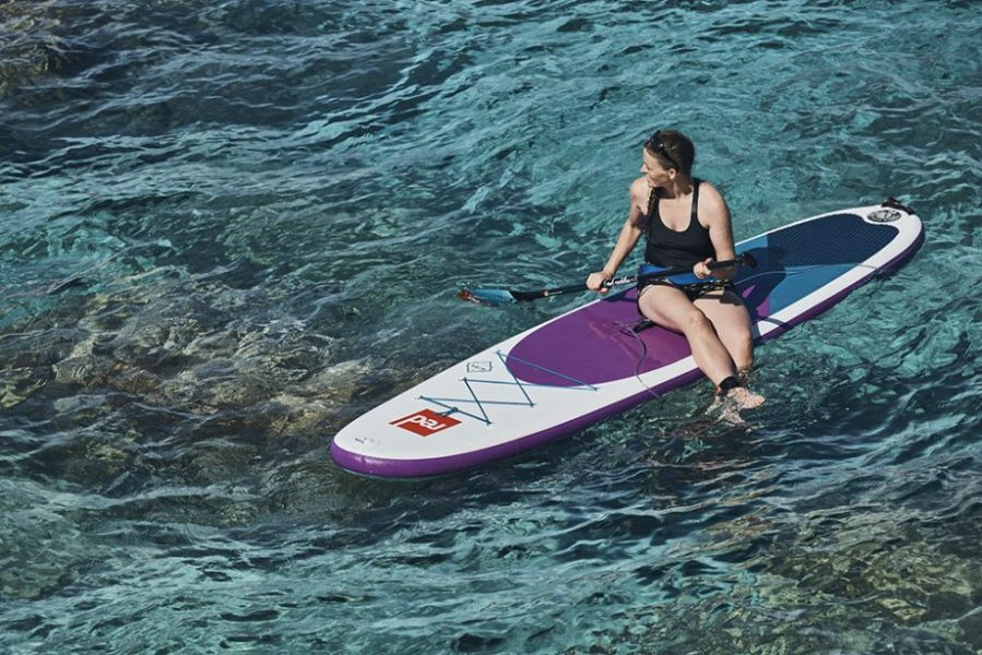 woman sitting on a red paddle co inflatable paddle board ride 10 6 SE