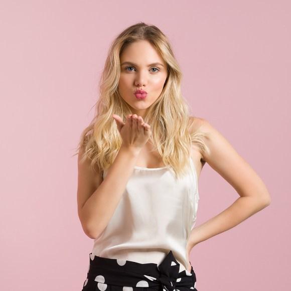 Print de Gif modelo feminina loira mandando beijo em fundo rosa