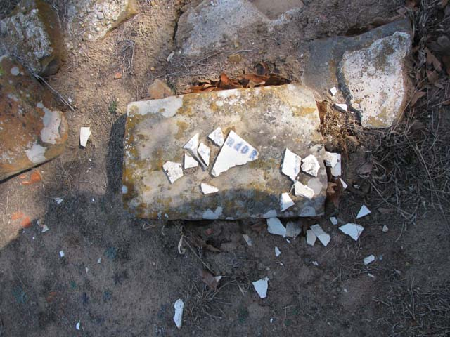 """Just below the headstone lie shards of a fairly old, white plate. I could make out the name """"Langdon"""" on it. The name was stenciled on the plate in blue, and then was glazed and fired, so the plate may have been a family heirloom. The deceased boy's last name was Langdon."""