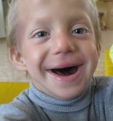 PD: Brody smiles a huge, open-mouthed smile into the camera, close-up. He has sandy blonde hair & blue eyes, wearing a gray turtleneck sweater.