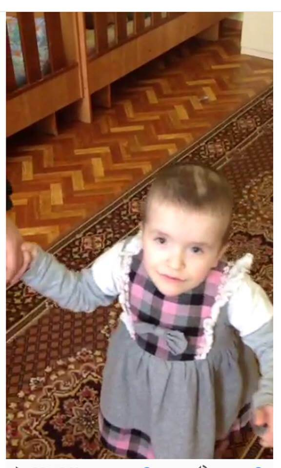 PD: Anna stands on carpet, holding a caregiver's hand. She wears a gray dress w/ pink plaid hem & front, ruffle sleeves, & a big bow. Her hair is shaved short & she looks directly into the camera w/ a mischievous look on her sweet face!
