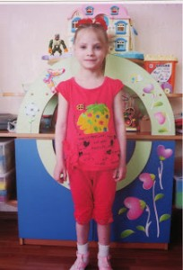 PD: Casey stands in front of some colourfully-decorated play equipment, wearing a pink outfit. She has a bow in her long, blonde ponytail.