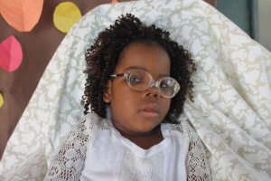 PD: Jubilee wears a white dress w/ lace detail. She has tightly-curled hair & big, brown eyes. She wears glasses.