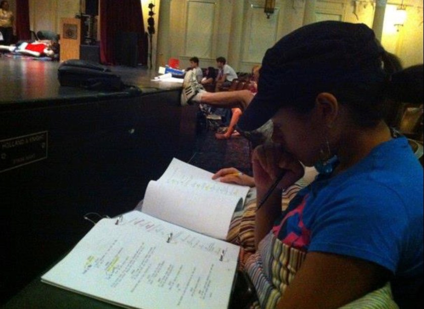 Photo of Tamara Austin studying a play