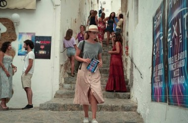 Image of Zoe Walker (Laura Haddock) walking through narrow street with map in hand. She is looking at posters on the wall of EXIT IBIZA night club.