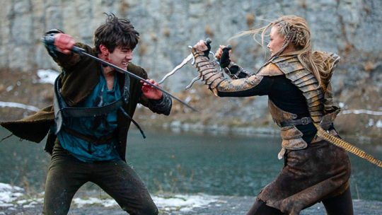 Jack Kane (Lukas, Left)  fights with a sword against Carolina Carlsson (The Snake, Right) who holds a dagger in each hands.