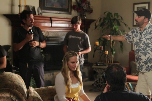 Image shows Abraham Martínez standing left with light meter. A director stands right pointing. Other cast and crew sit and stand around.