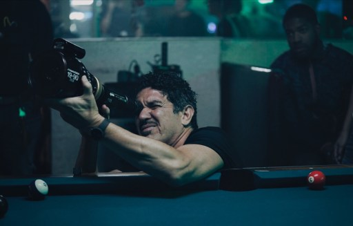 Image shows Abraham Martínez holding a camera up to his right eye while leaning on a pool table. He is facing to the left. There are two pool balls on the table and one other person standing further back to his left.