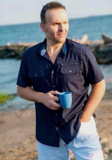Photo shows Alex Ziwak on a beach in blue shirt, holding a light blue mug in his right hand and looking to the right