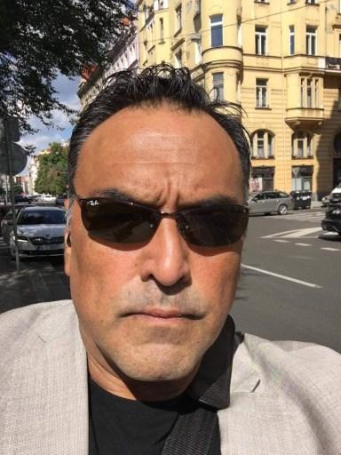 Image shows Dan Bradford in a street in Prague, Czech Republic. He is wearing sunglasses.