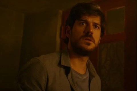 A scene from Invisible City of Eric wearing a green shirt to match his eyes.