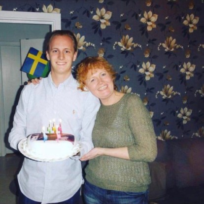 Photo of David S. Lindgren (left) and his mother Ewa Lindgren (right) with a birthday cake and candles. Swedish flag to the left.