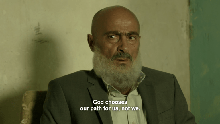 """An older Middle Eastern man in a suit and open collar sits looking to his right slightly; he has no head hair but has a grey moustache and generous beard. The walls behind him show wear and tear in green paints. Caption reads: """"God chooses our path for us, not we."""""""