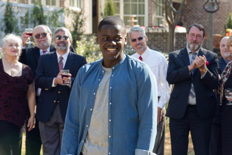 A picture of Daniel Kaluuya smiling amidst a crowd in a scene from the 2017 horror film Get Out.