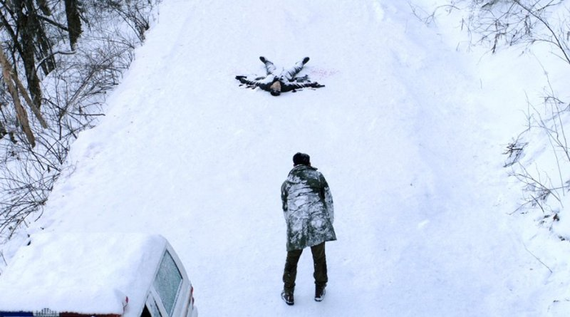 A man stands in front of a dead body in a snow-covered road.