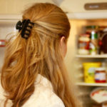 woman looking in open fridge