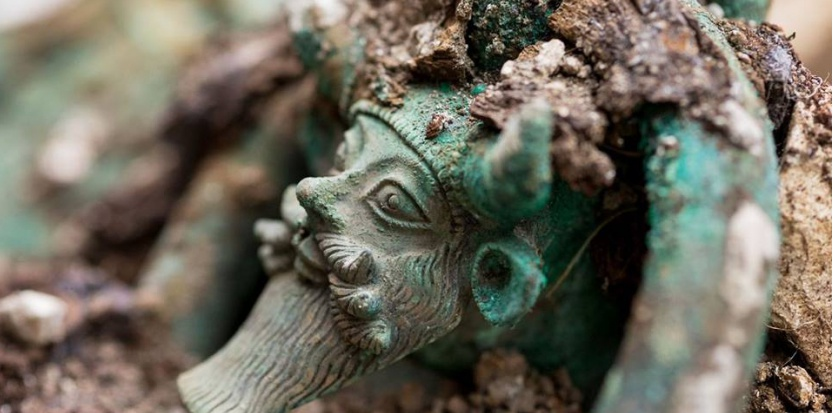 """""""Au fond de la tombe, découverte d'un chaudron en bronze, aux anses décorées du dieu Acheloos. Fouille de Lavau (Aube)"""", écrit l'Inrap sur sa page Facebook. (© Denis Gliksman, Inrap)"""