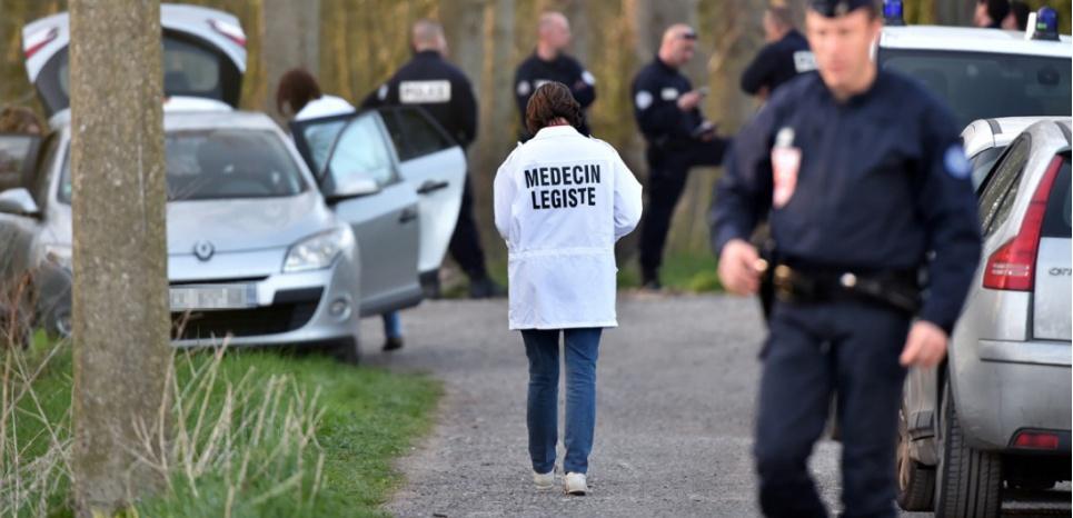 Un médecin légiste dans la forêt de Dubrulle, à Calais, où a eu lieu le meurtre de la petite Chloé mercredi 15 avril. (AFP / PHILIPPE HUGUEN)