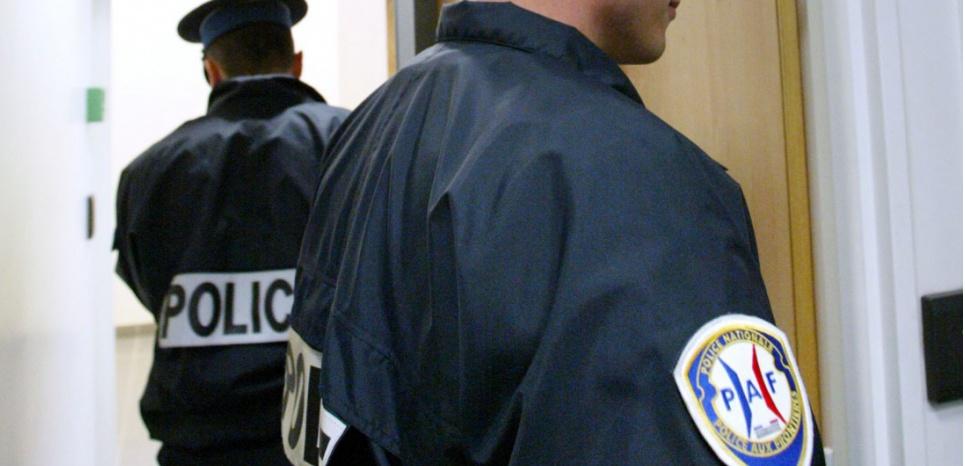 Des membres de la PAF (Police de l'air et des frontières) sont en faction, le 6 octobre 2003, dans la zone d'attente de l'aéroport de Roissy-Charles de Gaulle. (DANIEL JANIN/AFP)