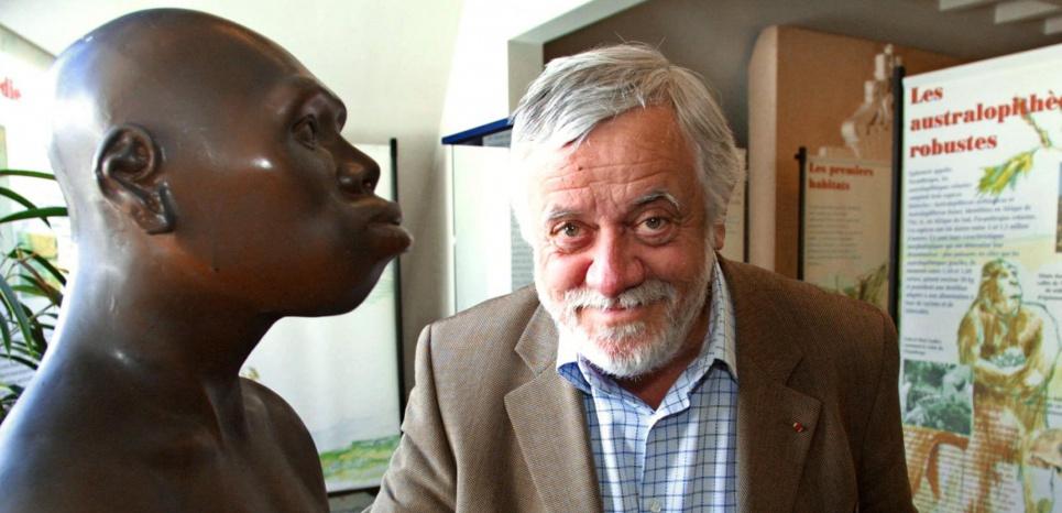 """Le paléontologue français Yves Coppens pose dans le cadre de l'exposition """"Lucy à Carnac"""", le 10 juillet 2004 près d'une reconstitution de Lucy, australopithèque dont les ossements originaux sont conservés au musée d'Addis Abeba. © FRED TANNEAU / AFP"""