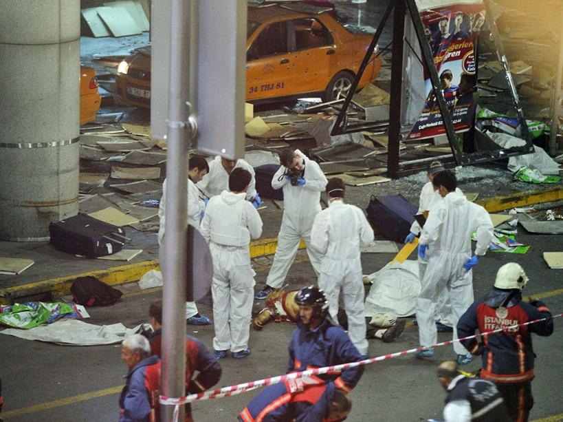 Des experts autour d'une des victimes de l'attentat de l'aéroport.