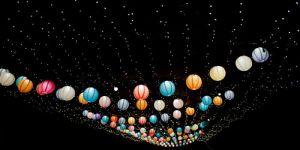 Coloured lighted lanterns hanging in a dark street