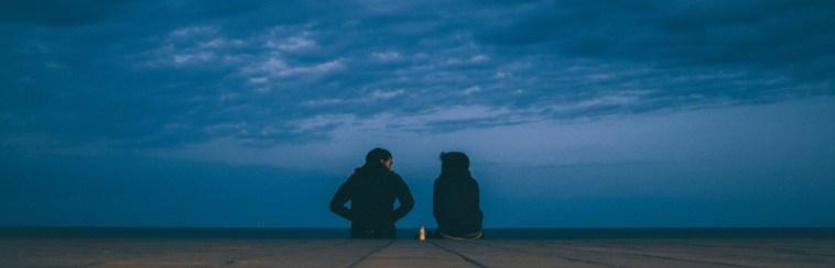 Twee mensen die op de grond zitten met een donkere bewolkte lucht erboven