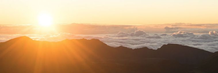 Zonsopgang, waarbij de zon achter een wolkendek en een `berg vandaan komt