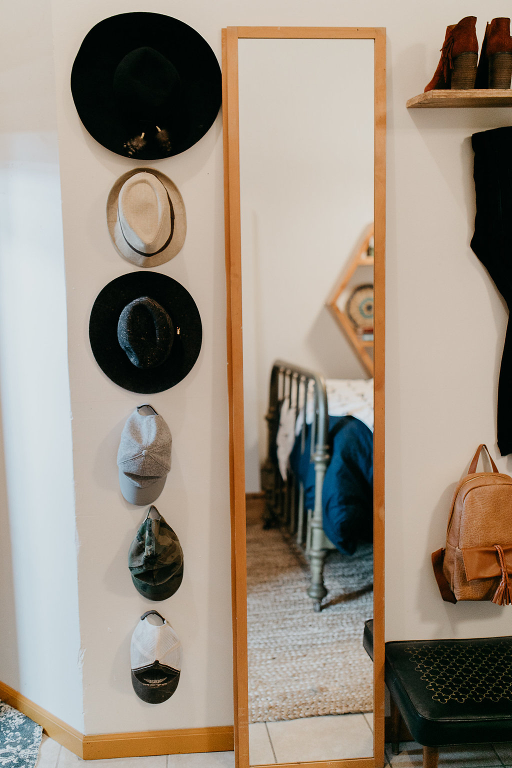 Hats hanging on the wall next to a floor length mirror