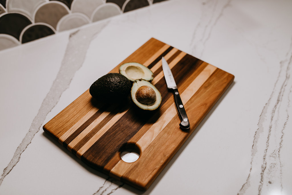 Avocado on multi wood stained cutting board