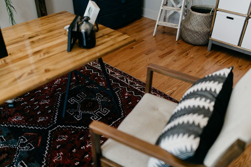 Red, black, and white printed rug and wooden furniture