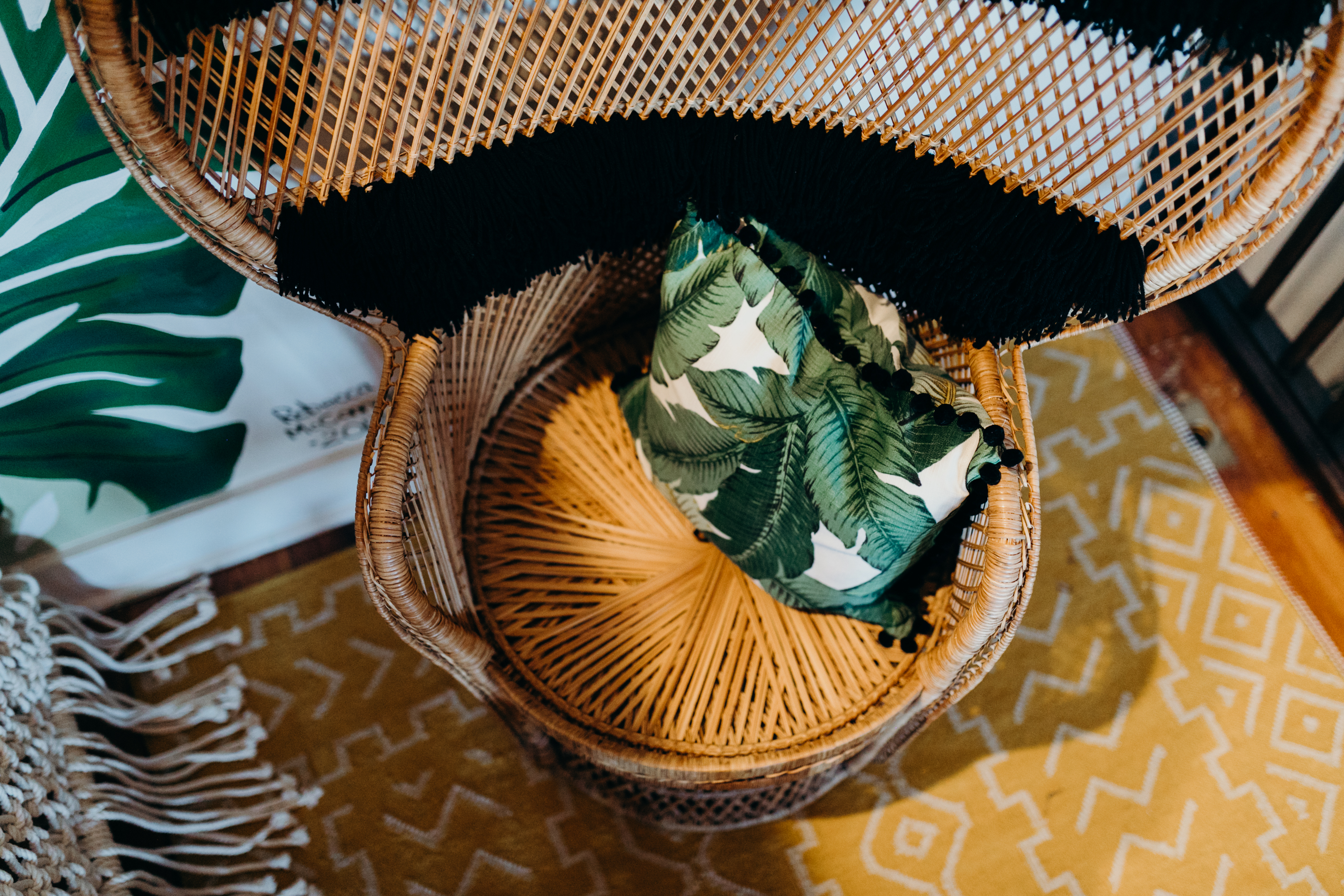 Airbnb, wicker chair with fringe and leaf pillow