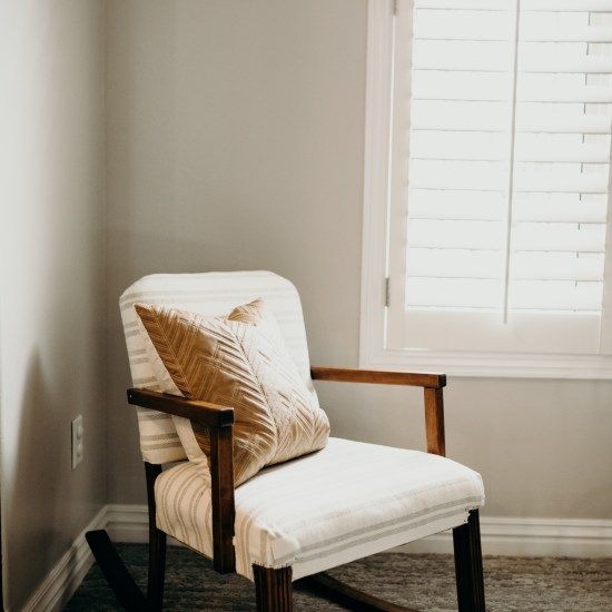 White cushion wood rocking chair with pillow