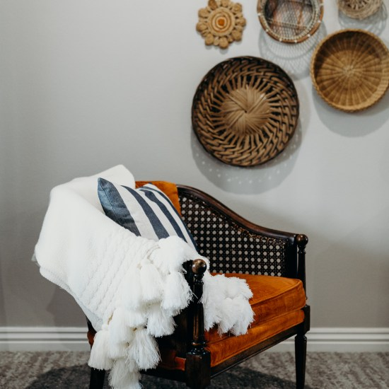Orange cushioned wood chair and wall decor