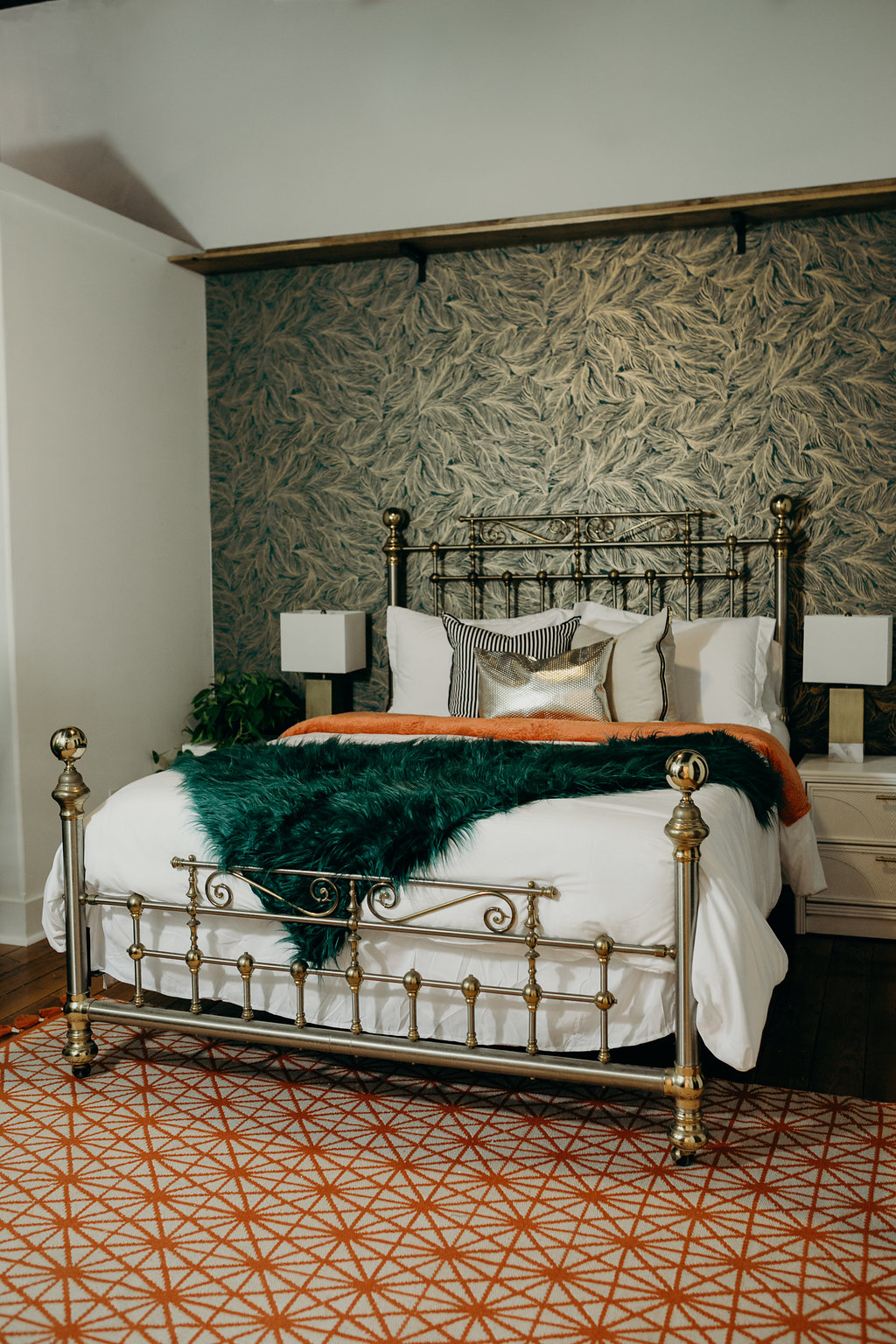 Queen bed, orange and green throws, green wallpaper, springfield airbnb