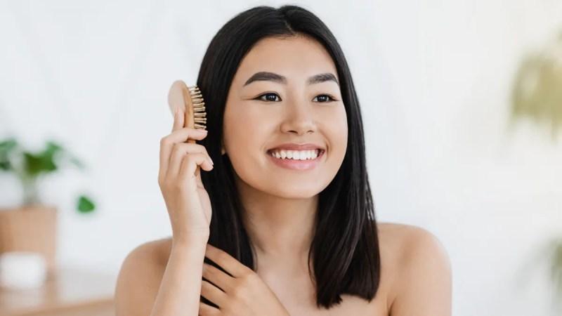 Asian American woman brushing hair