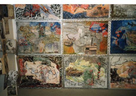 Ausstellungsdetail: Gerahmte Bilder, dicht an dicht gehängt, links im Bild ein Ensemble.