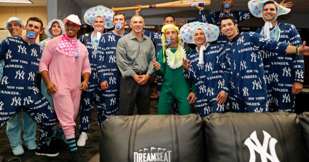 Manager Joe Girardi, center, poses with rookies dressed in Yankees onesies for their charter flight to Toronto following the game against the Tampa Bay Rays on Sept. 22, 2016, in St. Petersburg, Florida. (Photo by Mike Carlson/Getty Images)