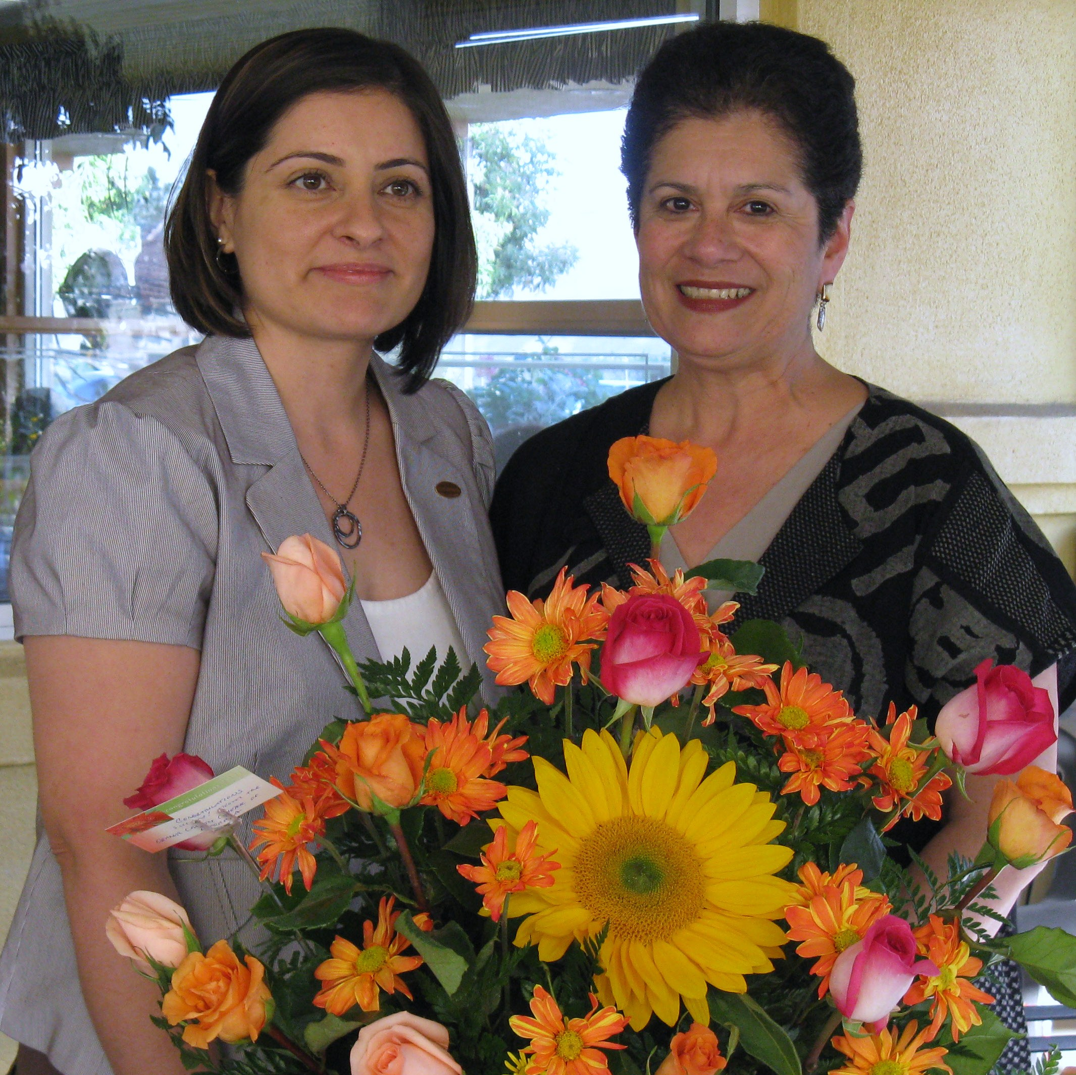 OC Chapter President Monica Lopez presents flowers to 2009 LOTY recipient, Susan Luevano