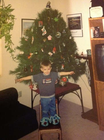 My son showing off the Christmas tree.