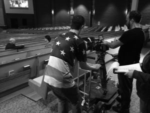Joshua Justice, Assistant Cameraman, operates the doorway dolly as he and Kevin Hayes, Director of Photography, get a shot of Sherry Morris and Bill Ritchie as they discuss what can happen when you remove God from the equation of life.
