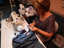 Amy tightens shoulder straps on a dress she's working on. Amy says you have to be careful with the fabric since it isn't easy to work with.