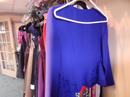 Dresses placed on a rack at Noor's Alterations. Wesal Muhi, who goes by Amy, designed these dresses herself.