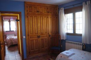 Habitación azul con dos camas, amplia y con gran armario.