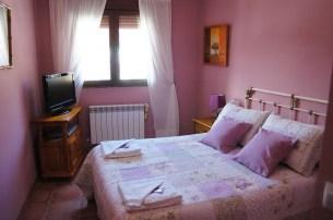 Habitación rosa con Tv y baño.
