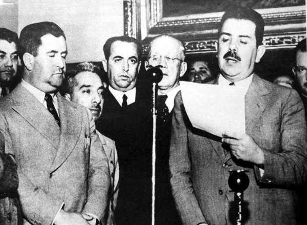El presidente Lázaro Cárdenas del Río lee el decreto de expropiación petrolera en el balcón central de Palacio Nacional, durante la magna manifestación de apoyo, el 23 de marzo de 1938