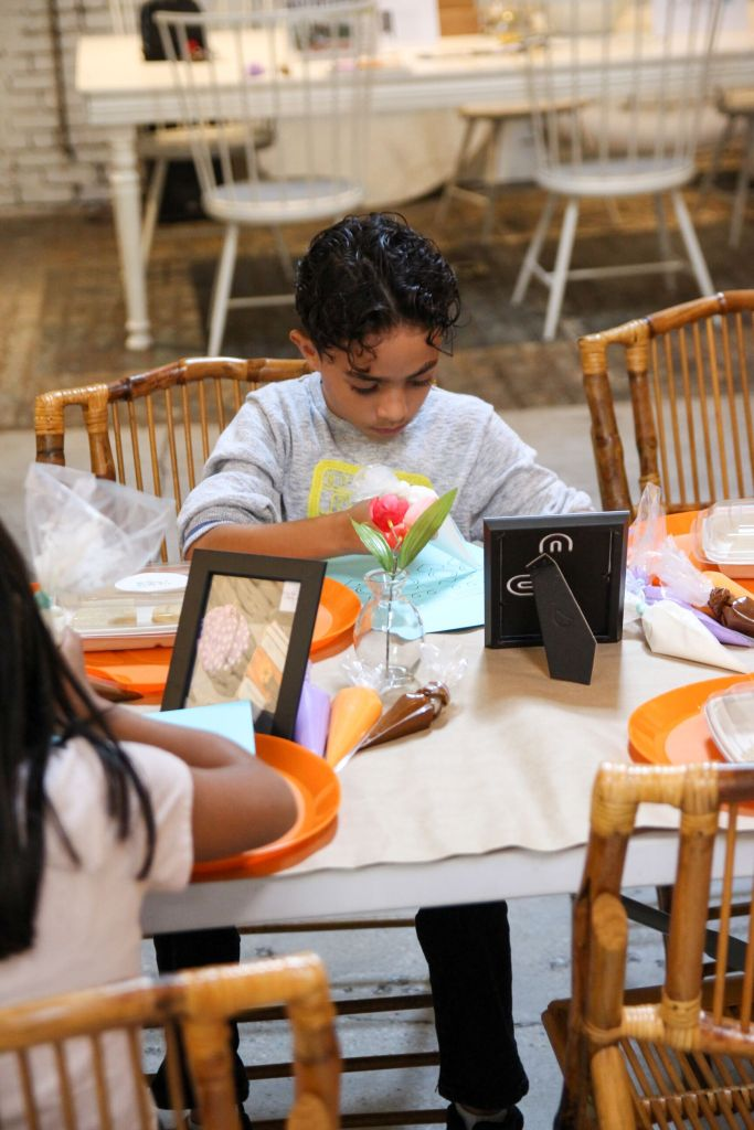 Child intently practices frosting at an educational workshop for youth on custom desserts at Regency Event Venue