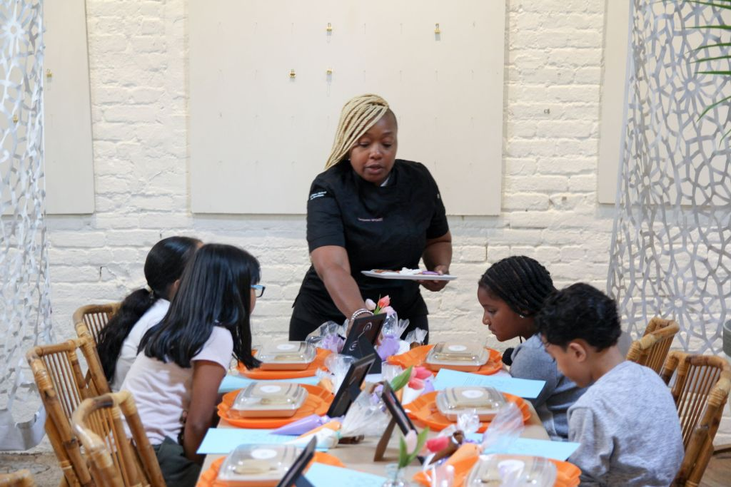 Woman serves desserts at educational workshop for youth on custom desserts